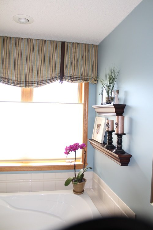 Faux roman shade valance over a soaking tub in master bathroom. Blue, tan and brown striped faux silk fabric with a decorative brown faux silk bow. All fabric from Fabricut/Trend.