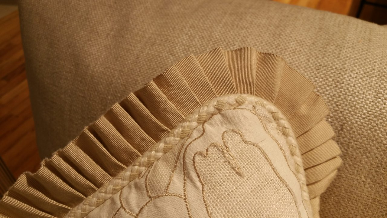 Decorative linen pillow with pleated grosgrain ribbon and braided cord on the perimeter.