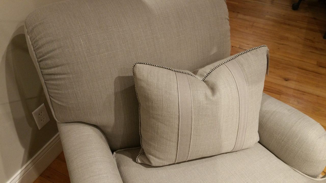 Linen upholstered chair with decorative linen pillow with decorative herringbone tape and bead chain cord around perimeter.