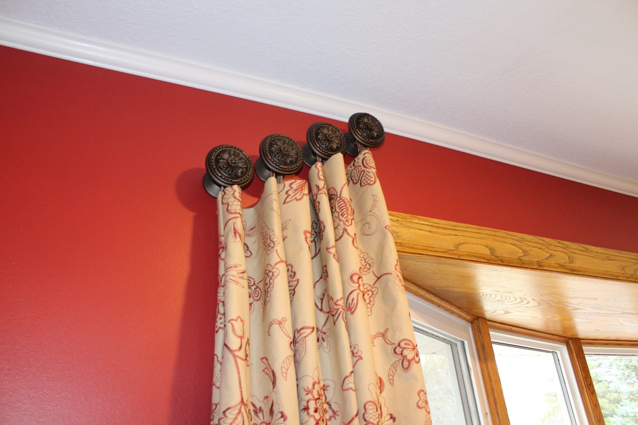 Angled drapery panels made with a red embroidered tan cotton blend fabric from Trend with decorative medallions.
