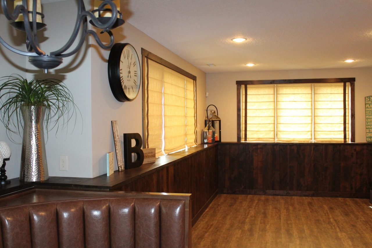 The basement recreation area has a custom built in leather channeled banquette in the lower left corner. The window treatments are cordless flat roman shades fabricated with a tan linen with a strip of banding on both the left and right of each window.