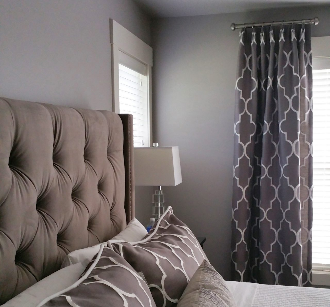 Master bedroom with tufted upholstered velvet headboard. Pinched, pleated to pattern drapery panels with Fabricut and Trend fabric on decorative drapery hardware from Forest Group Drapery Hardware. The same fabric was used for the king sized pillow shams with white velvet welt cord.