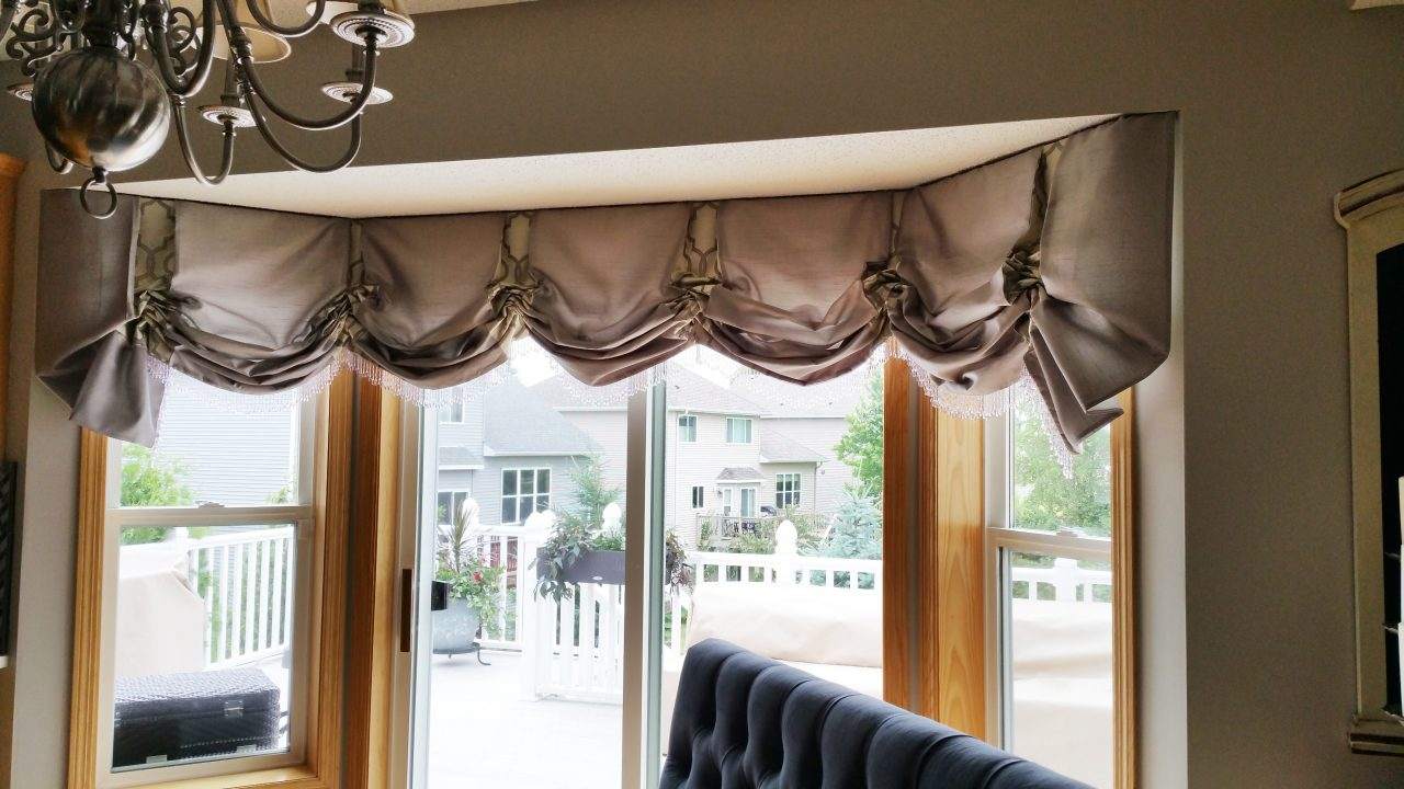 Slouch valance treatment on a bay window with contrast fabric within the pleats and beaded trim on the bottom.