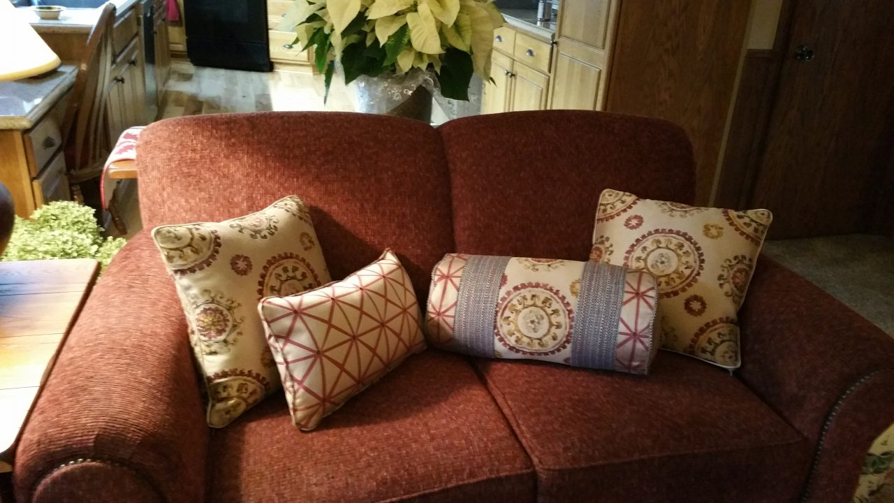 Decorative pillows on upholstered couch. Suzani print, tweed fabric, Fabricut fabric