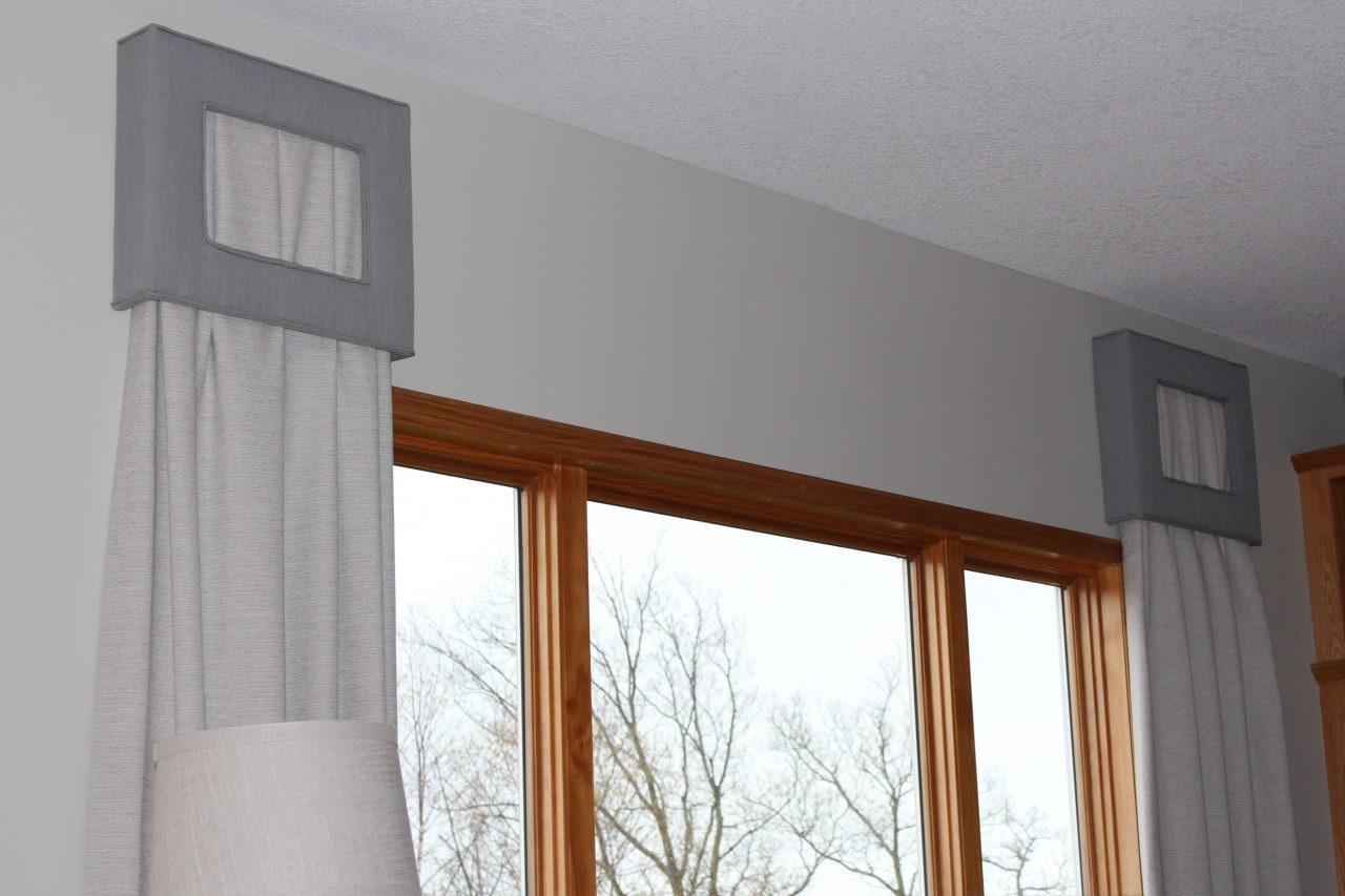 Rectangular linen cornices with cut outs in the front and welt cord around the perimeter. Stationary faux silk drapery panels hung from inside the cornice bow. Fabric from Fabricut and Trend.