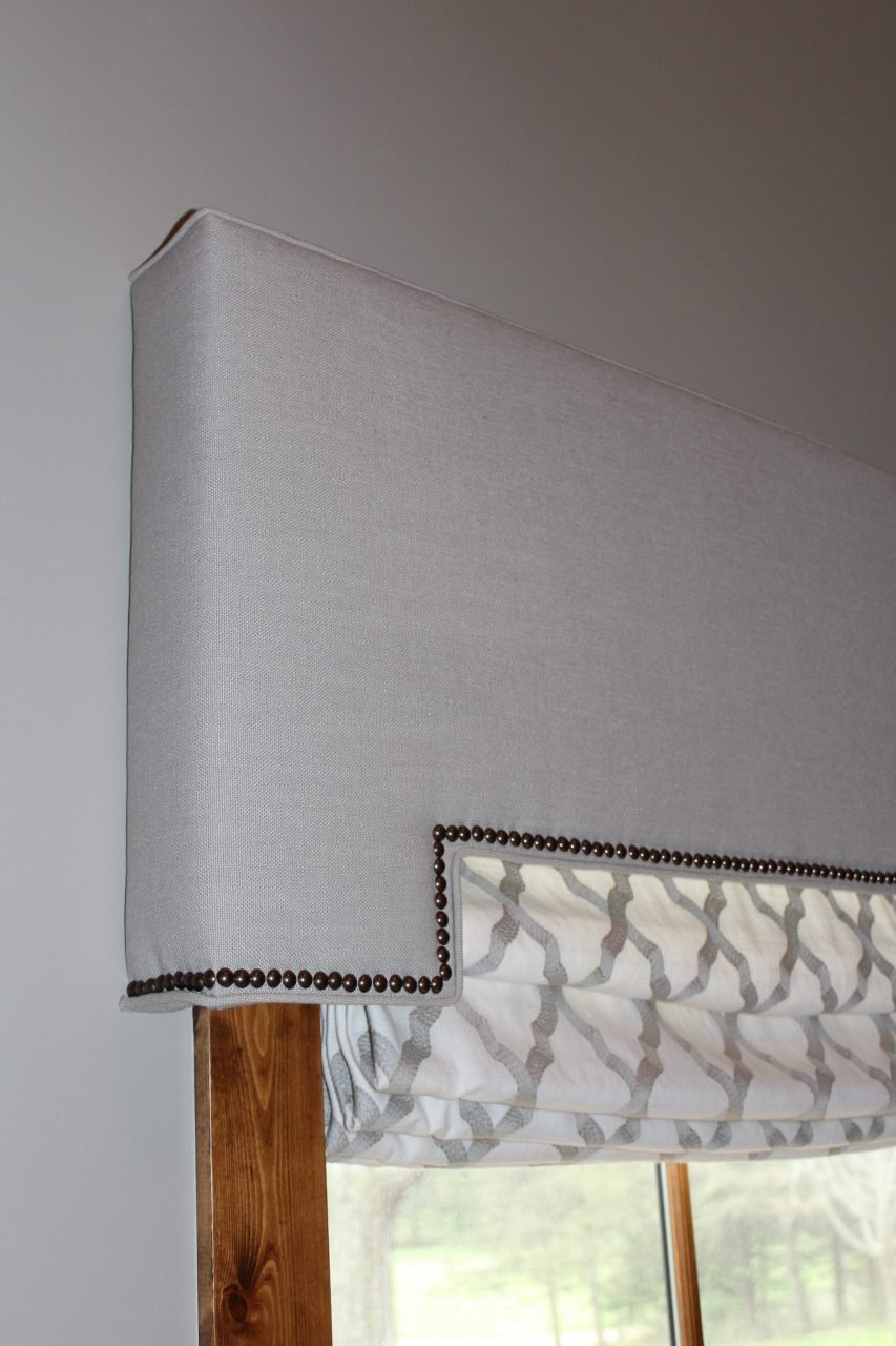 Living room windows covered with linen fabric covered cornices and self-welt and nail heads on the bottom edge. Underneath the cornices there are cordless roman shades created with a tone on tone cotton herringbone fabric with geometric embroidery. Fabrics from Fabricut and Trend.