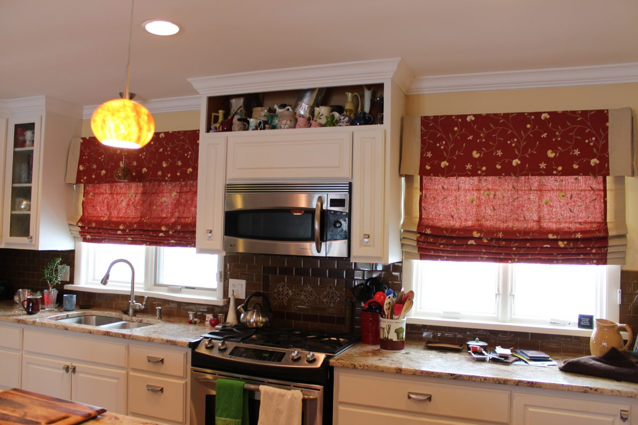 Kitchen windows with cordless roman shades. Red linen fabric with tan embroidered floral and tan banding on the left and right of each shade.