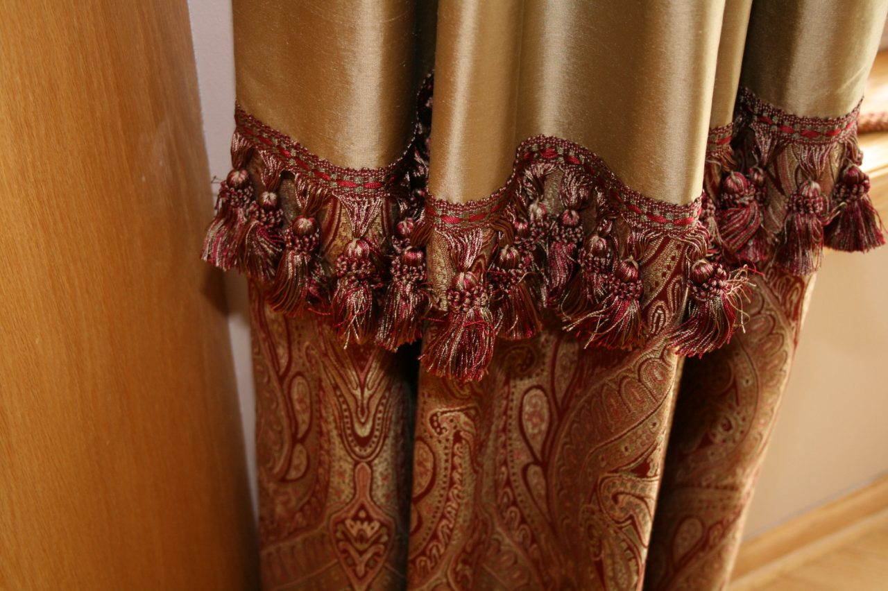 Stationary decorative drapery panels with gold dupioni silk fabric on top portion and paisley fabric on bottom portion, separated with a fringe in between. RM Coco fabrics and trim