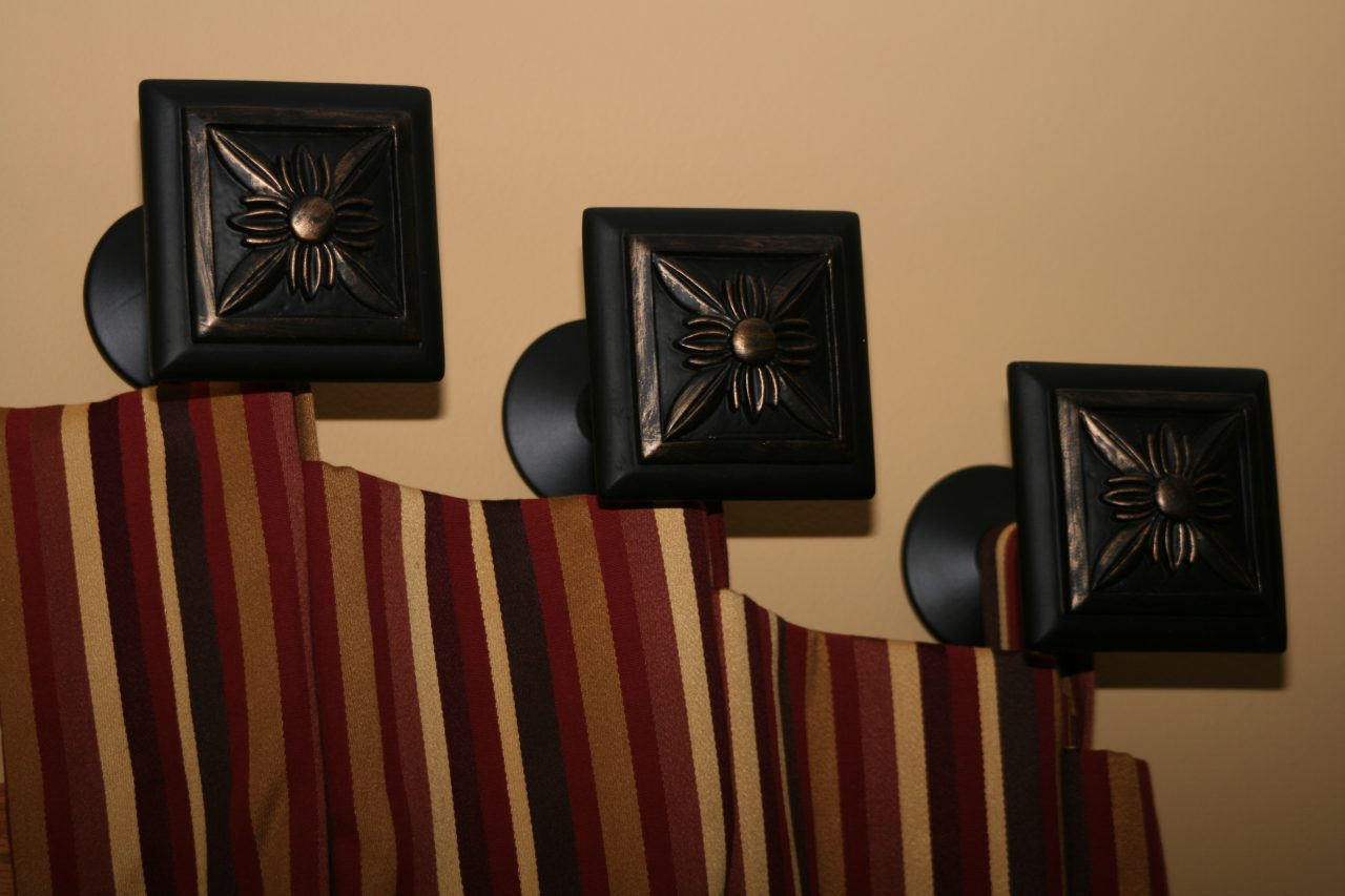 Angled drapery panels in a striped RM Coco fabric. Paris Texas hardware medallions.