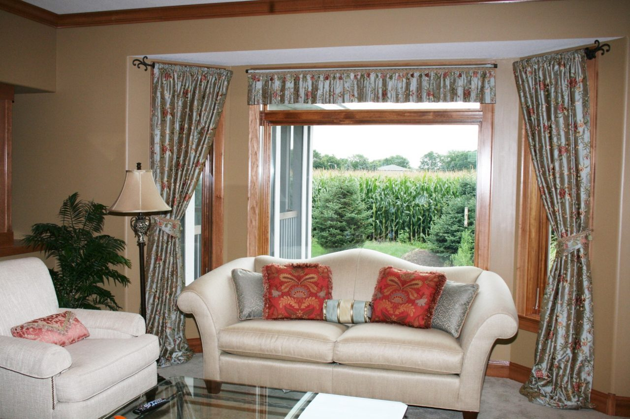 Using a embroidered silk from India, we created a luxurious combination of puddling rod pocket panels, held back with decorative custom holdbacks in the same fabric. Pleated valance was made to cover transom window slightly, highlighted by a feminine trim towards the top.  All drapery hardware is from Robert Allen. Pillows on couch were also fabricated in a similar palette to coordinate with the new bay window treatment.