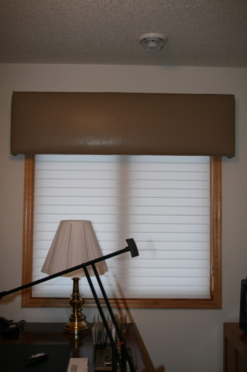 Simple straight cornice covered with a tan snakeskin vinyl. Underneath there is a Hunter Douglas Powerview silhouette blind with a 3 inch vane.