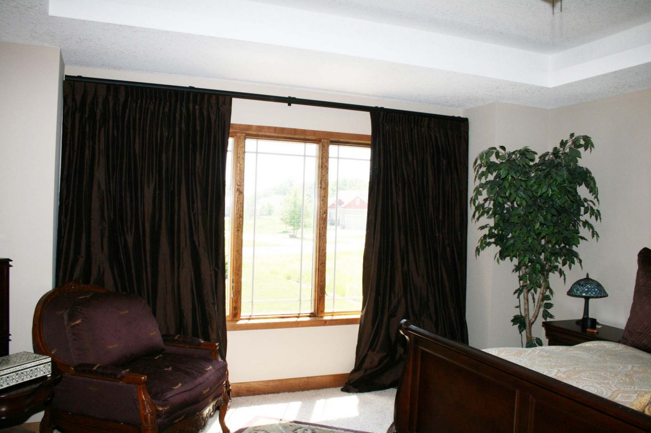 Operable french blackout operable draperies fabricated with chocolate brown dupioni silk. Helser Brothers Ruffino track wrought iron hardware.