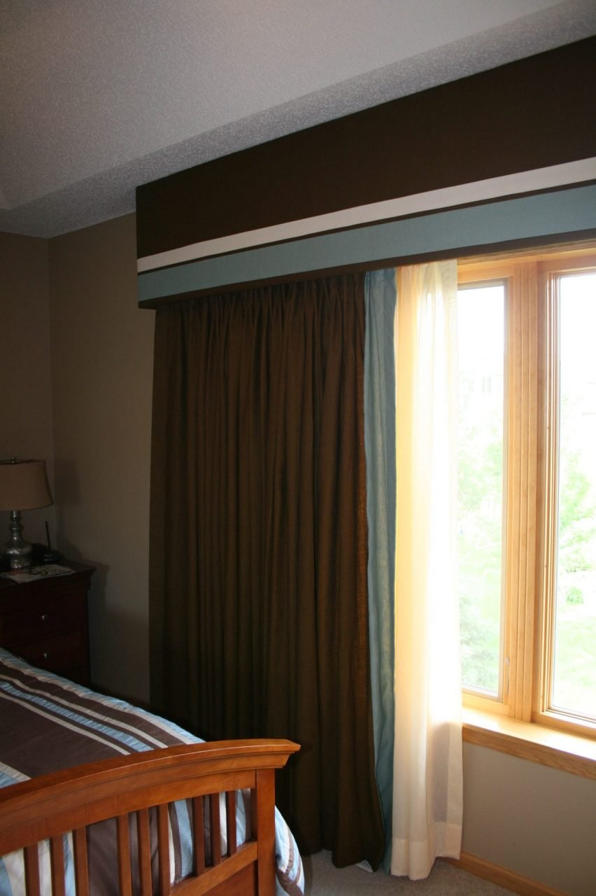 Master bedroom window with a linen wrapped cornice, contrasting stripes, matching drapery panels with contrast leading edge and sheers underneath.