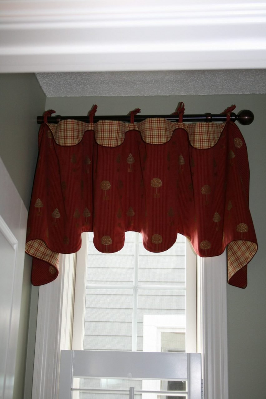 Bathroom window with faux wood shutters covered with floppy top valance with ties. Aria drapery hardware.