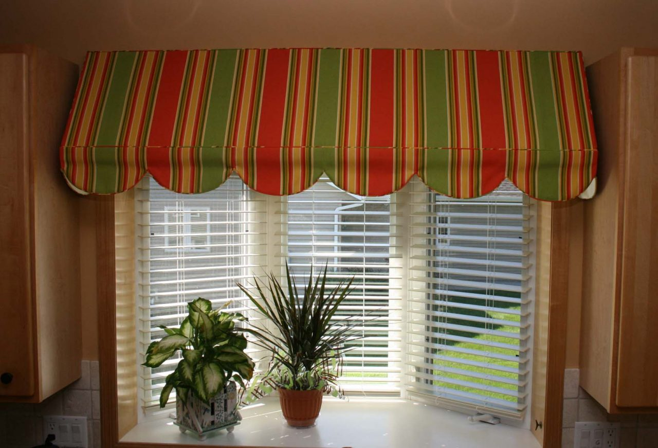 Indoor awning created with a striped fabric over a kitchen sink bay window, Hunter Douglas Everwood alternative wood blinds.