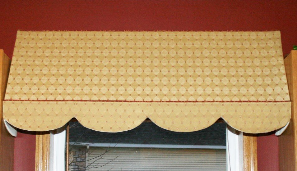 An indoor awning, placed between 2 cabinets. A scalloped bottom is added to the bottom portion, separated by a contrasting but coordinated welt cord.