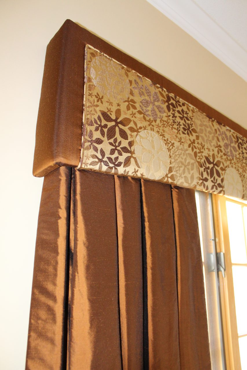 This custom cornice is made with duppioni silk direct from India. The pattern portion is inset and surrounded by a welt cord along the perimeter. The stationary drapery panels are lined with interlining and lining to add to the body of the pleats.