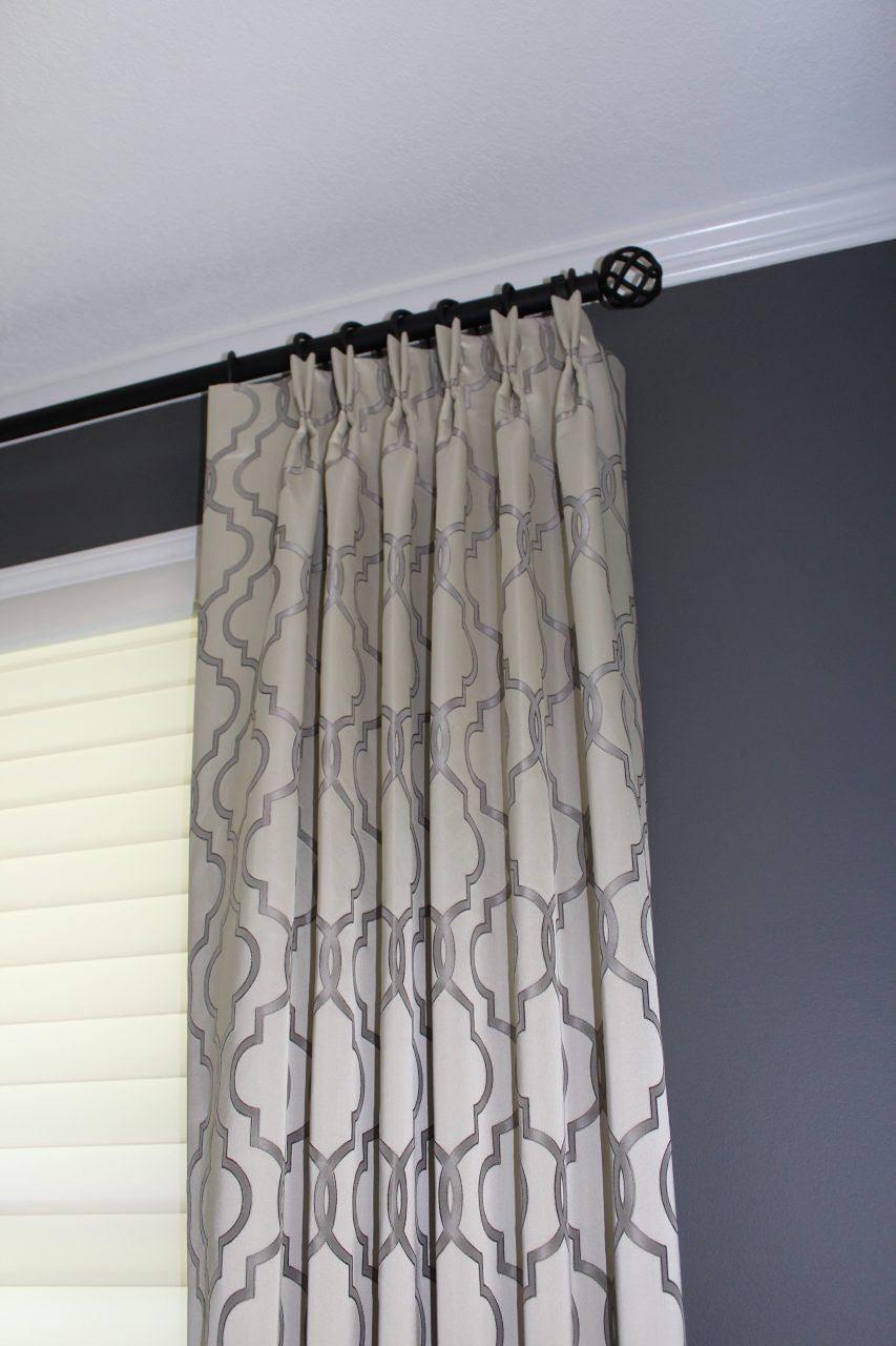 "A stationary side panel, pleated to pattern, 3 finger pinched pleats made with Trend brand fabric. Panels are hung on wrought iron decorative drapery hardware from Helser Brothers.  The undertreatment is an inside mounted Hunter Douglas Silhouette blind, 3""vanes, with Ultraglide 2 control."
